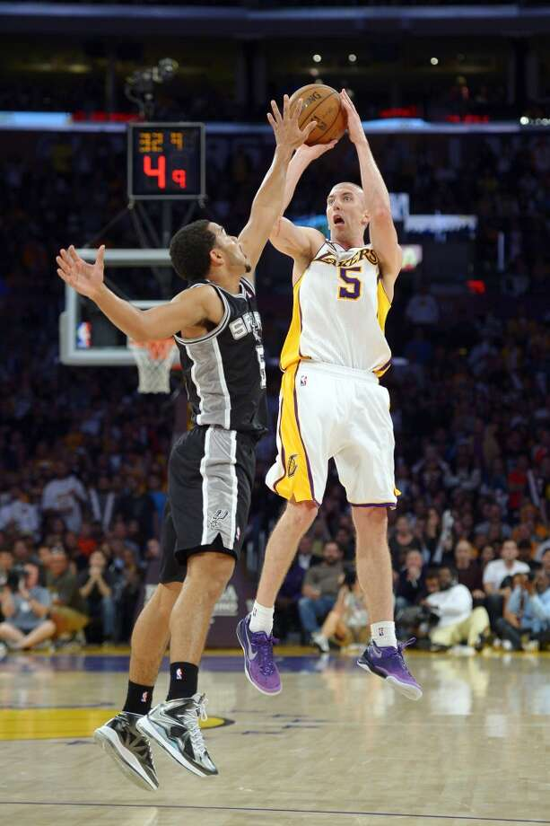 Los Angeles Lakers guard Steve Blake (right) shoots as Spurs guard Cory Joseph defends during the second half  Sunday, April 14, 2013, in Los Angeles. Blake scored 23 points as the Lakers won 91-86.
