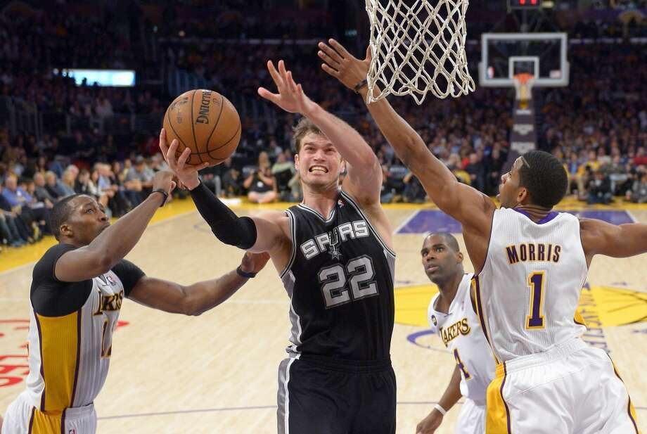 Spurs center Tiago Splitter (center)  puts up a shot as Los Angeles Lakers center Dwight Howard (left) and guard Darius Morris defends as forward Antawn Jamison looks on during the second half  Sunday, April 14, 2013, in Los Angeles. The Lakers won 91-86.
