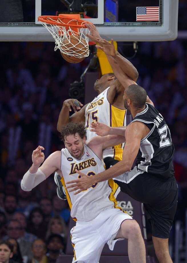 Spurs forward Tim Duncan (right) dunks over Los Angeles Lakers forward Metta World Peace (top left) and forward Pau Gasol during the second half  Sunday, April 14, 2013, in Los Angeles. The Lakers won 91-86.