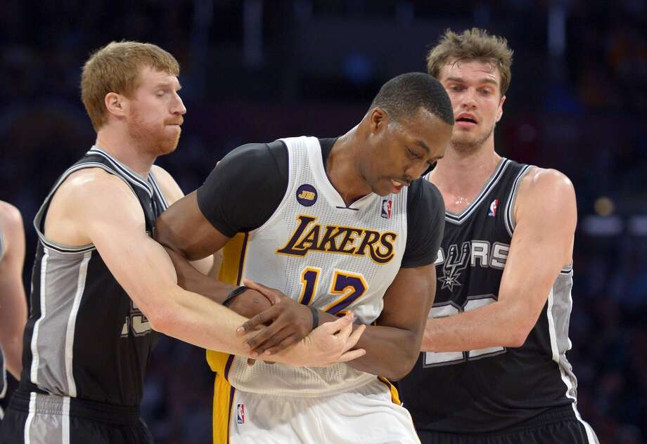 Los Angeles Lakers center Dwight Howard (center) is intentionally fouled by Spurs forward Matt Bonner (left) and center Tiago Splitter during the second half  Sunday, April 14, 2013, in Los Angeles. The Lakers won 91-86.