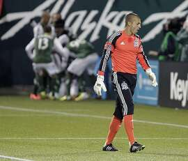 San Jose Earthquake goalie Jon Busch walks back toward the goal as the Portland Timbers celebrate scoring against him on a penalty kick during the second half of an MLS soccer game in Portland, Ore., Sunday, April 14, 2013.  The Timbers won 1-0.(AP Photo/Don Ryan)