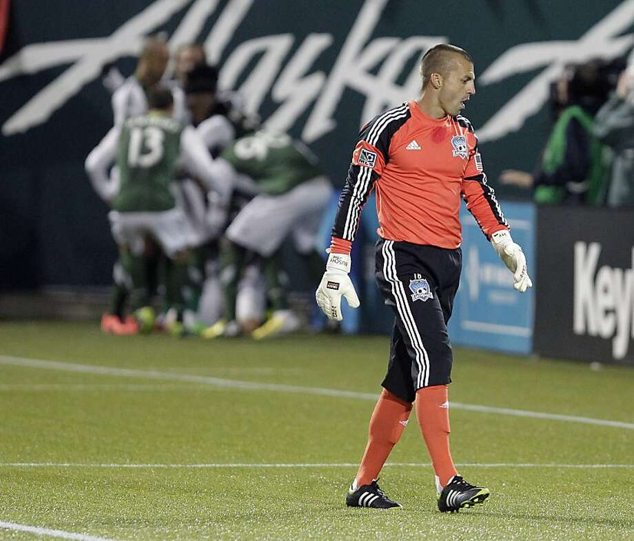 Earthquakes goalkeeper Jon Busch can only walk away as the Timbers (background) celebrate the game's only goal on a free kick in the 78th minute. Photo: Don Ryan, Associated Press