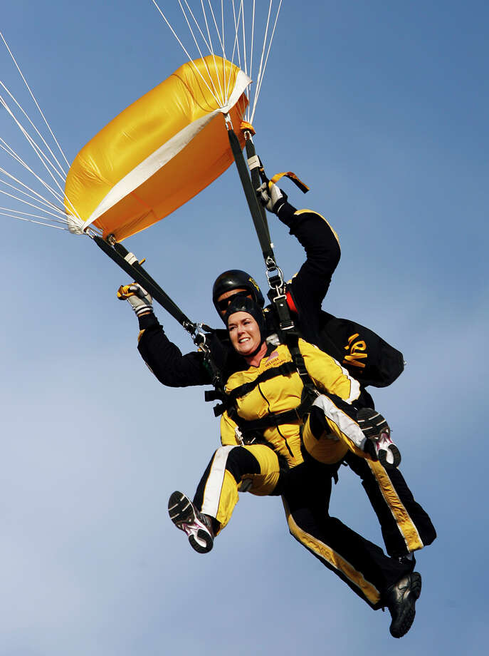 Syndicated columnist Heloise (Ponce Cruse Evans) descends to earth with tandem parachuter Sgt. 1st Class Mike Elliott of the U.S. Army Golden Knights Parachute Team at Stinson Municipal Airport on January 2, 2008. The parachute team often take people up in tandem jumps to show the Army's appreciation as well as to educate citizens about military skydiving.  Photo: KIN MAN HUI, San Antonio Express-News / kmhui@express-news.net