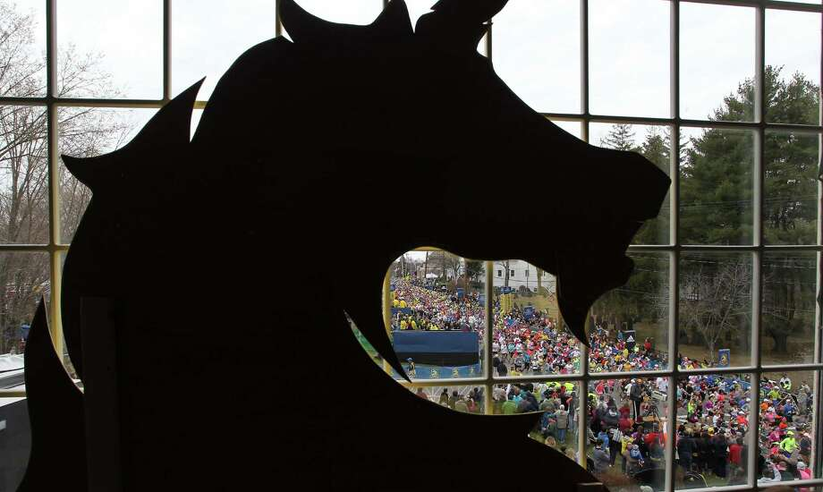 Behind a silhouette of the Boston Athletic Association logo, runners start the 117th running of the Boston Marathon, in Hopkinton, Mass., Monday, April 15, 2013. (AP Photo/Stew Milne) Photo: Associated Press
