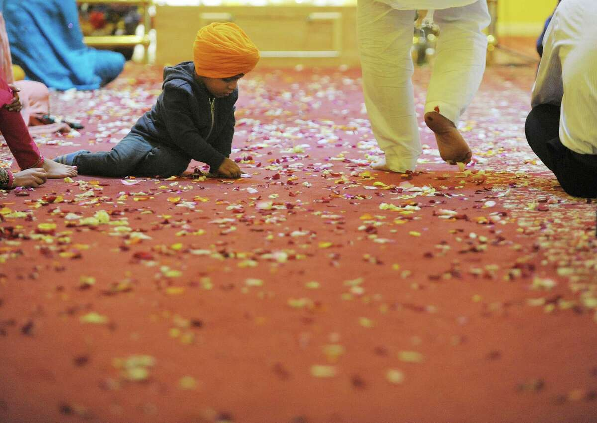 Ather Singh, 3, plays with some flower petals on the floor of the temple during a celebration of Vaisakhi Gurpurab at the Niskayuna Gurdwara Sahib temple on Sunday, April 14, 2013 in Niskayuna, NY. The three day event celebrates the gathering of the sangat for Vaisakhi at Sri Anandpur Sahib Ji in 1699, that produced a fundamentally important spiritual event in Sikh history. The temple which is in its second year, held events from Friday through Sunday. Political leaders along with members of law enforcement were also on hand on Sunday to be honored and to talk to members of the community. About 150 families belong to the temple. (Paul Buckowski / Times Union)