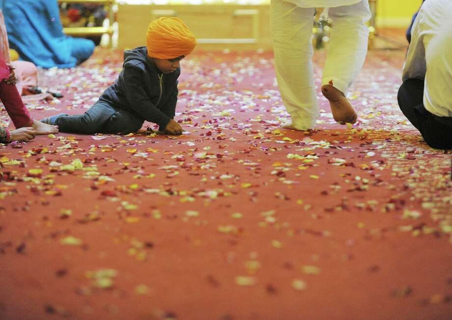 Ather Singh, 3, plays with some flower petals on the floor of the temple during a celebration of Vaisakhi Gurpurab at the Niskayuna Gurdwara Sahib temple on Sunday, April 14, 2013 in Niskayuna, NY. The three day event celebrates the gathering of the sangat for Vaisakhi at Sri Anandpur Sahib Ji in 1699, that produced a fundamentally important spiritual event in Sikh history.  The temple which is in its second year, held events from Friday through Sunday.  Political leaders along with members of law enforcement were also on hand on Sunday to be honored and to talk to members of the community.  About 150 families belong to the temple.    (Paul Buckowski / Times Union) Photo: Paul Buckowski