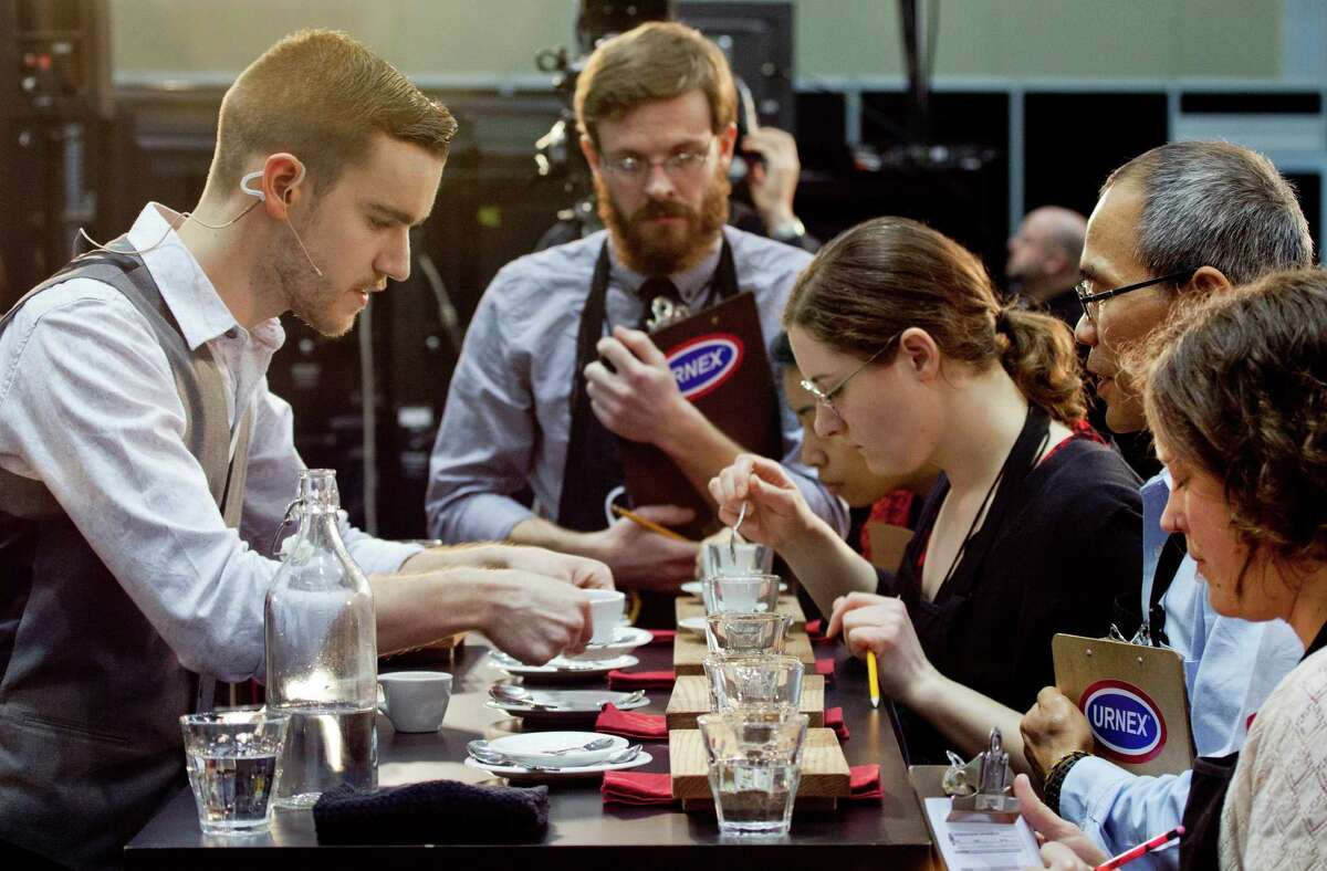 In this Thursday, April 13, 2013 photo, barista competitor Nick Purvis, left, of Santa Barbara, Calif., presents one of his brewed entries to a panel of judges at the annual United States Barista Championship in Boston. Participants have 15 minutes to prepare and serve four espressos, four cappuccinos and four signature beverages, as they compete for a chance to go to the world championship in Melbourne, Australia.