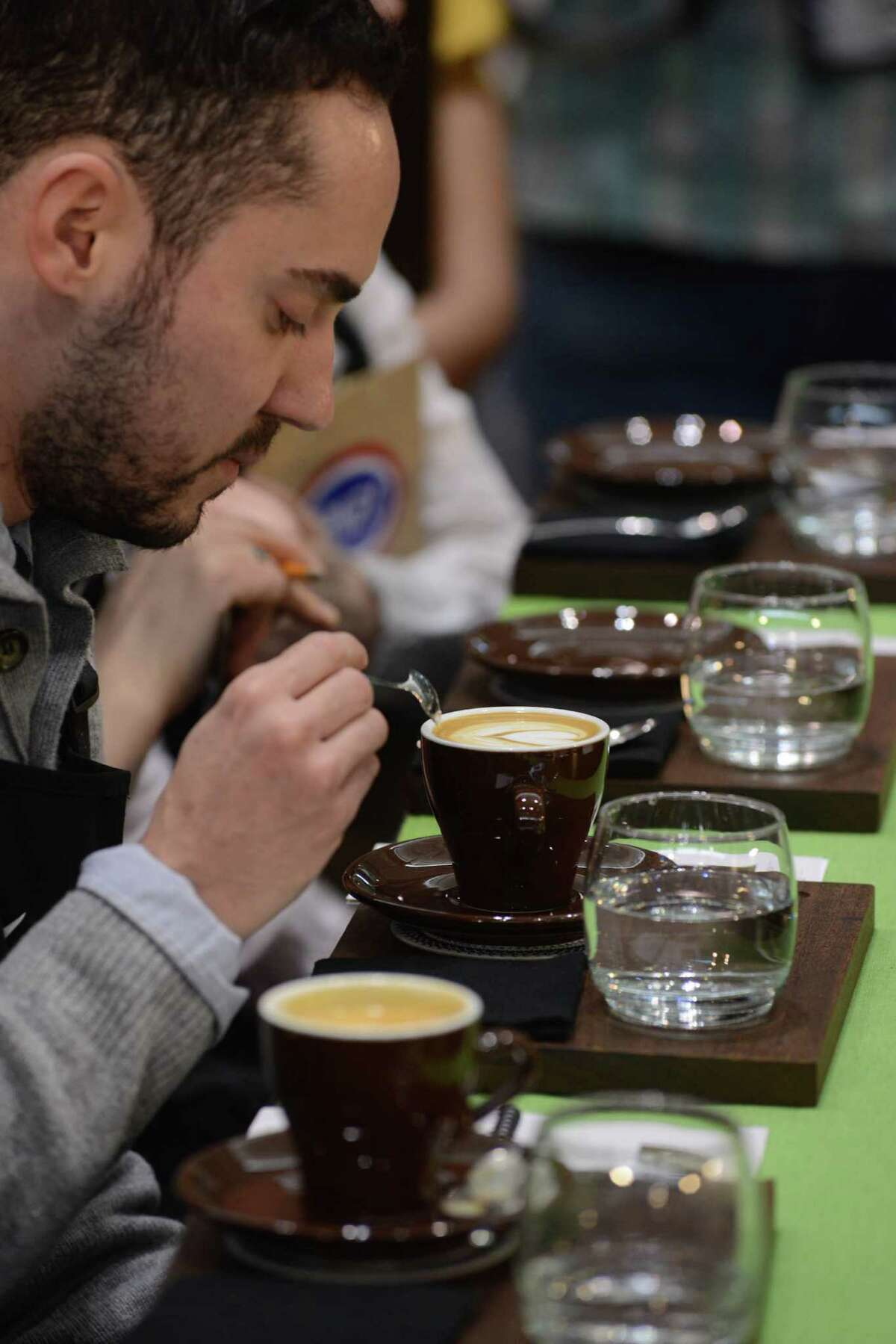 BOSTON - APRIL 13: Judges test coffee during the U.S. Barista Championships at the Coffee Industry Expo at the Boston Convention and Exhibition Center April 13, 2013 in Boston, Massachusetts. Fifty of the county's best baristas got 15 minutes to prepare and serve four espressos, four cappuccinos and four signature beverages to a panel of judges. The annual event brings in thousands of coffee lovers from around the country.