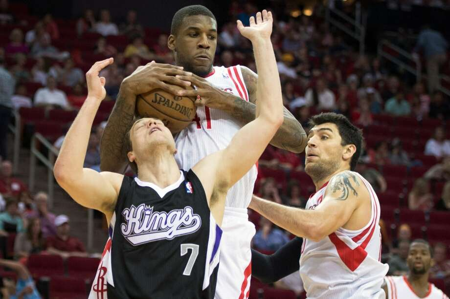 Rockets forward Thomas Robinson takes a rebound away from Kings point guard Jimmer Fredette. Photo: Smiley N. Pool, Houston Chronicle