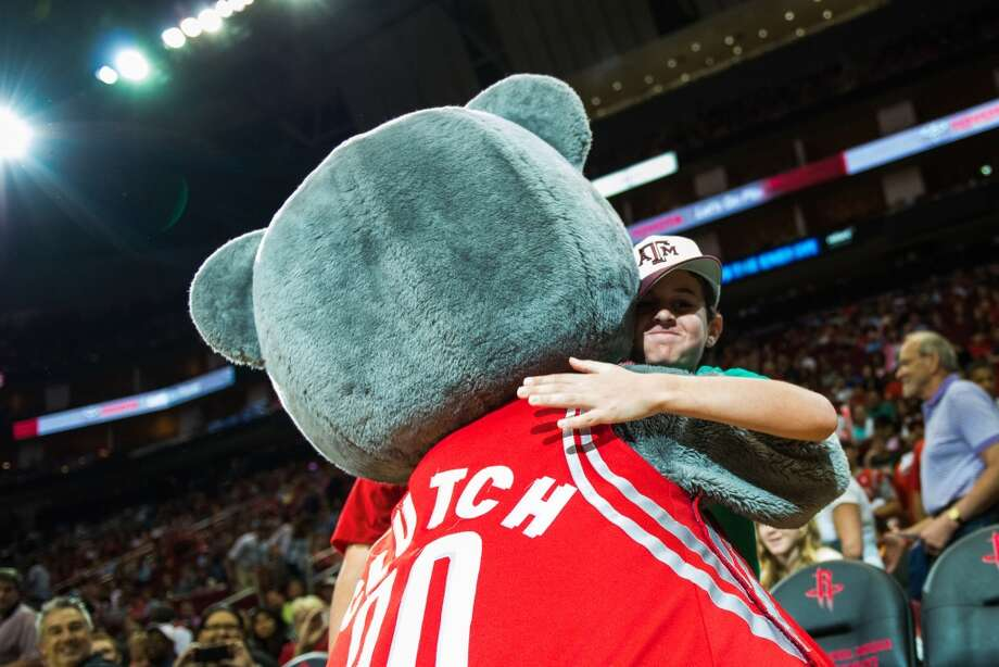 Rockets mascot Clutch hugs a young fan during the first half.
