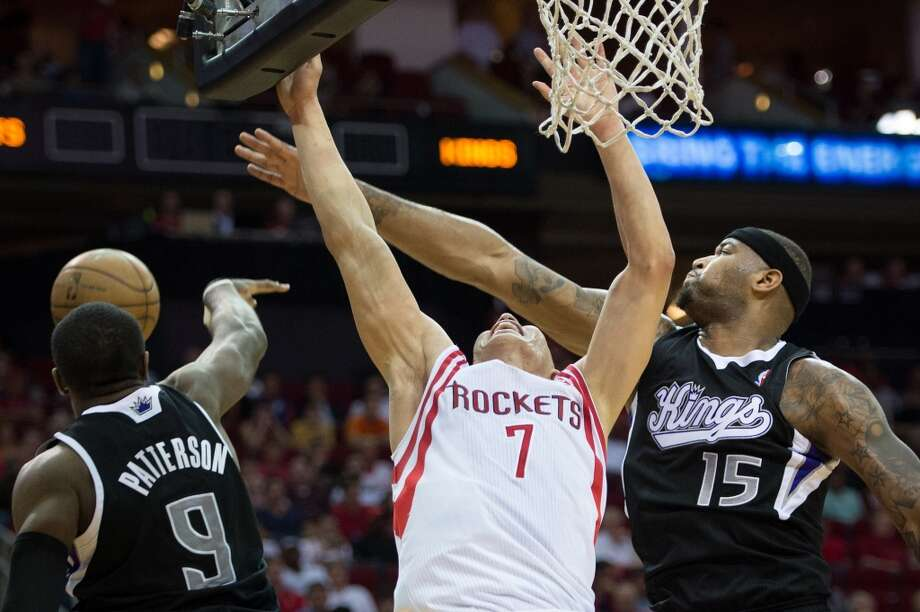 Rockets point guard Jeremy Lin (7) is fouled by Kings center DeMarcus Cousins (2) as power forward Patrick Patterson (9) defends.