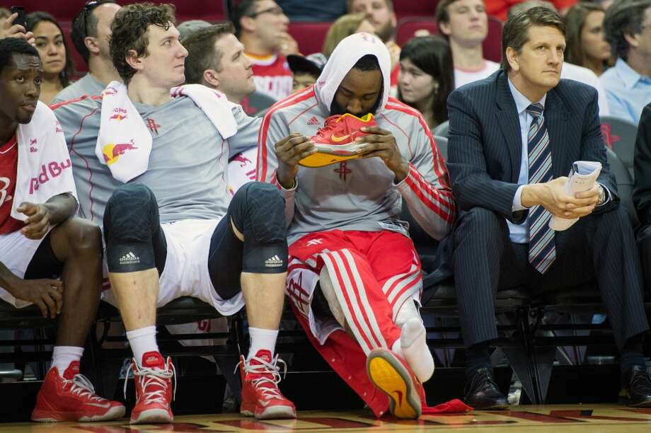 Rockets shooting guard James Harden examines his shoes on the bench during the second half.