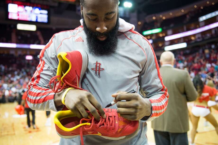 Rockets shooting guard James Harden autographs his shoes before giving them to 9-year-old Patrick DeClaire after the game. Photo: Smiley N. Pool, Houston Chronicle