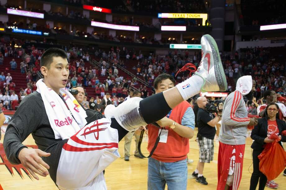 Rockets point guard Jeremy Lin kicks an autographed t-shirt into the crowd.