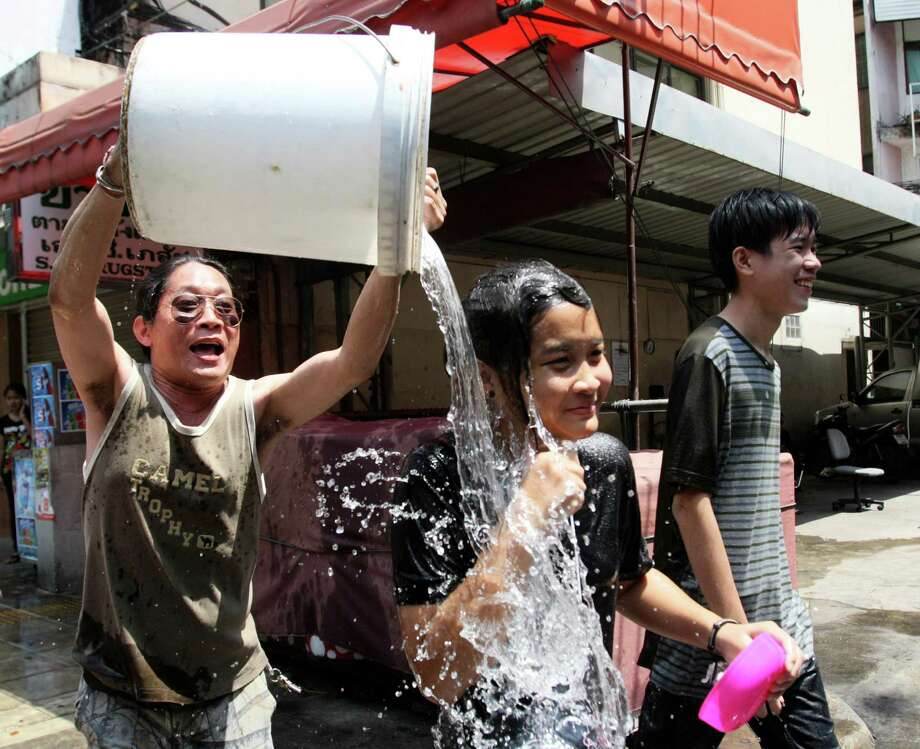 A Thai man pours a bucket of water on a girl during the Songkran festival to celebrate Thai New Year in Bangkok, Thailand, Saturday, April 13, 2013. (AP Photo/Sakchai Lalit) Photo: WIre