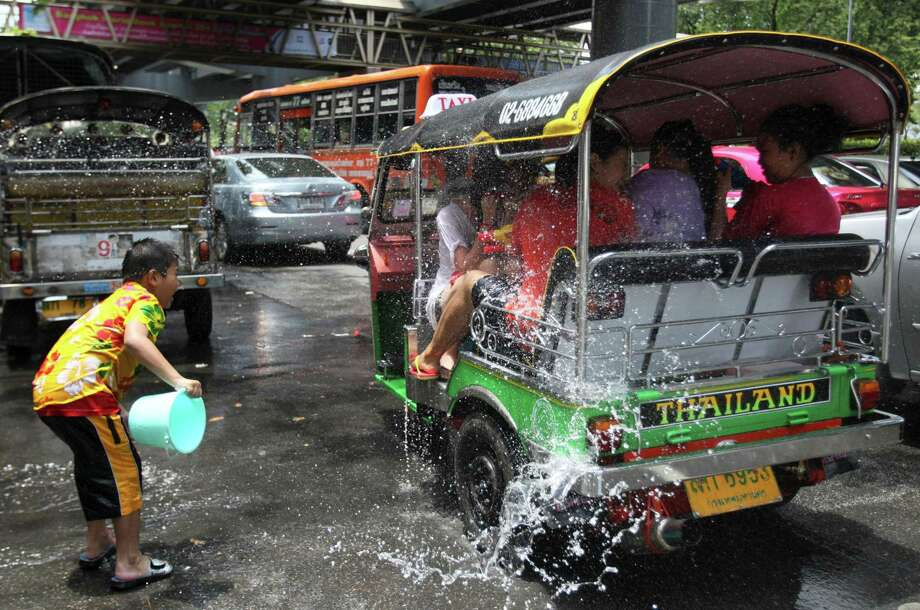 A Thai boy splashes water on passengers of a three-wheeled tax during the Songkran festival to celebrate Thai New Year in Bangkok, Thailand, Saturday, April 13, 2013. (AP Photo/Sakchai Lalit) Photo: WIre