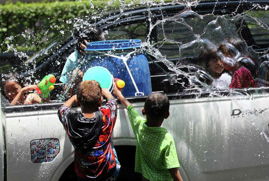 A Thai children splash water on people on the back of a truck during the Songkran festival to celebrate Thai New Year in Bangkok, Thailand, Saturday, April 13, 2013. (AP Photo/Sakchai Lalit) Photo: WIre