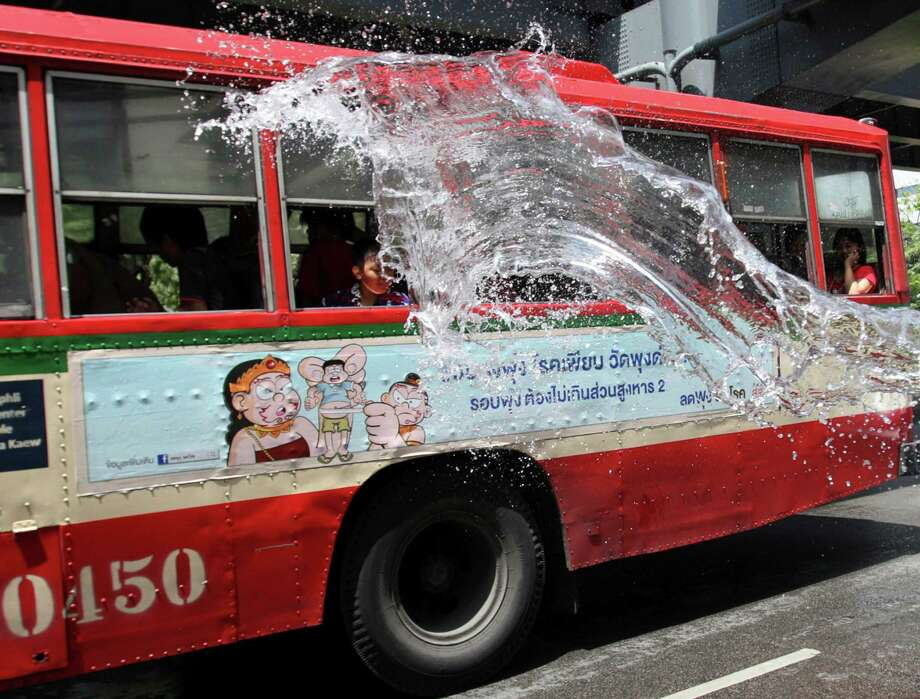 A Thai child splashes water on a bus during the Songkran festival to celebrate Thai New Year in Bangkok, Thailand, Saturday, April 13, 2013. (AP Photo/Sakchai Lalit) Photo: WIre