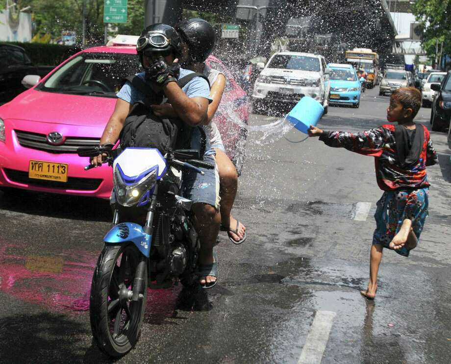 A Thai boy splashes water on motorcyclists during the Songkran festival to celebrate Thai New Year in Bangkok, Thailand, Saturday, April 13, 2013. (AP Photo/Sakchai Lalit) Photo: WIre