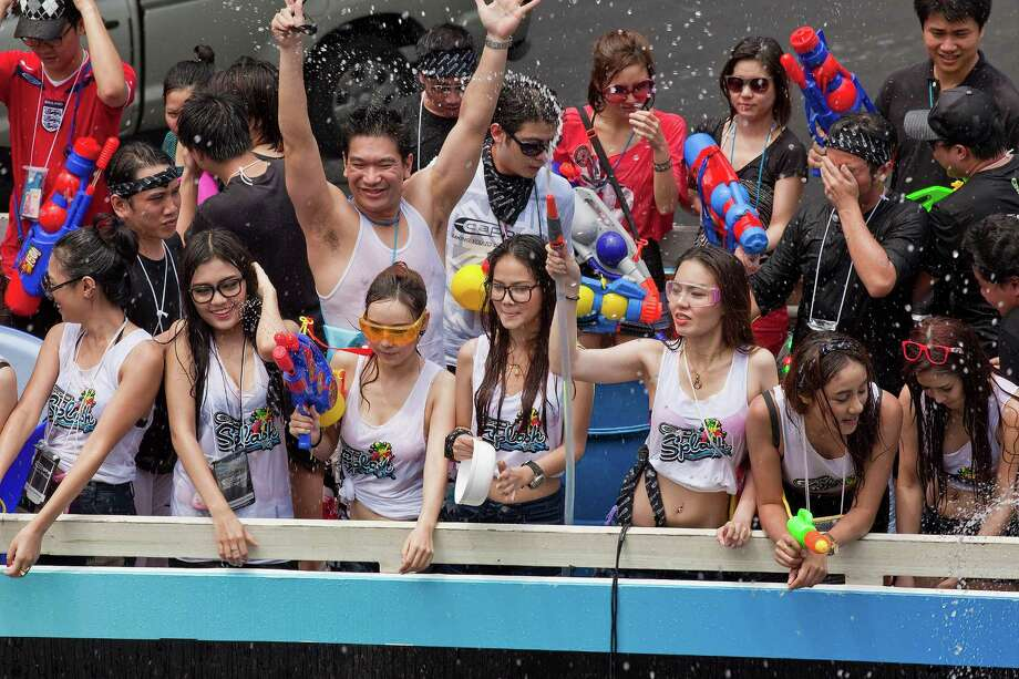 BANGKOK, THAILAND - APRIL 14:  People on a chartered bus participate in a community water fight on Silom Road as part of the Songkran water festival on April 14, 2013 in Bangkok, Thailand. The Songkran festival marks the traditional Thai New Year and is celebrated each year from April 13 to 15. The throwing of water originated as a way to pay respect to people and is meant as a symbol of cleansing and purification. (Photo by Jack Kurtz/Getty Images) Photo: Jack Kurtz, WIre / 2013 Getty Images