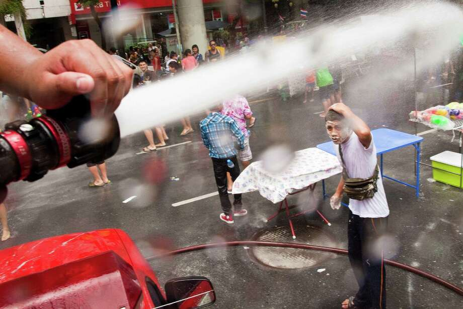 BANGKOK, THAILAND - APRIL 14:  A Bangkok firefighter squirts the crowd during a community water fight on Silom Road as part of the Songkran water festival on April 14, 2013 in Bangkok, Thailand. The Songkran festival marks the traditional Thai New Year and is celebrated each year from April 13 to 15. The throwing of water originated as a way to pay respect to people and is meant as a symbol of cleansing and purification. (Photo by Jack Kurtz/Getty Images) Photo: Jack Kurtz, WIre / 2013 Getty Images