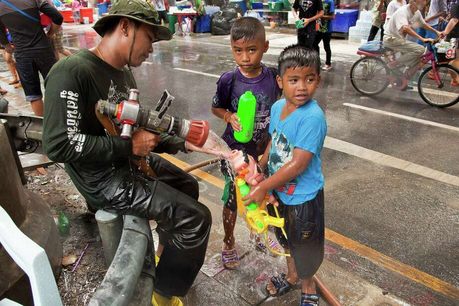 BANGKOK, THAILAND - APRIL 14:  Thai boys refill their squirt guns from a firefighter's hose during the Songkran water festival on April 14, 2013 in Bangkok, Thailand. The Songkran festival marks the traditional Thai New Year and is celebrated each year from April 13 to 15. The throwing of water originated as a way to pay respect to people and is meant as a symbol of cleansing and purification. (Photo by Jack Kurtz/Getty Images) Photo: Jack Kurtz, WIre / 2013 Getty Images