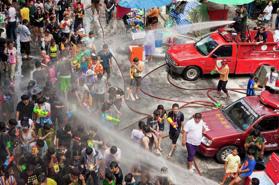 BANGKOK, THAILAND - APRIL 14:  Thai fire fighters soak the crowd with their fire hoses during a community water fight on Silom Road as part of the Songkran water festival on April 14, 2013 in Bangkok, Thailand. The Songkran festival marks the traditional Thai New Year and is celebrated each year from April 13 to 15. The throwing of water originated as a way to pay respect to people and is meant as a symbol of cleansing and purification. (Photo by Jack Kurtz/Getty Images) Photo: Jack Kurtz, WIre / 2013 Getty Images