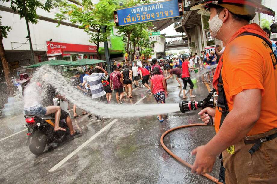 BANGKOK, THAILAND - APRIL 14:  A Bangkok fire-fighter soaks a couple riding a motorcycle through a community water fight on Silom Road as part of the Songkran water festival on April 14, 2013 in Bangkok, Thailand. The Songkran festival marks the traditional Thai New Year and is celebrated each year from April 13 to 15. The throwing of water originated as a way to pay respect to people and is meant as a symbol of cleansing and purification. (Photo by Jack Kurtz/Getty Images) Photo: Jack Kurtz, WIre / 2013 Getty Images