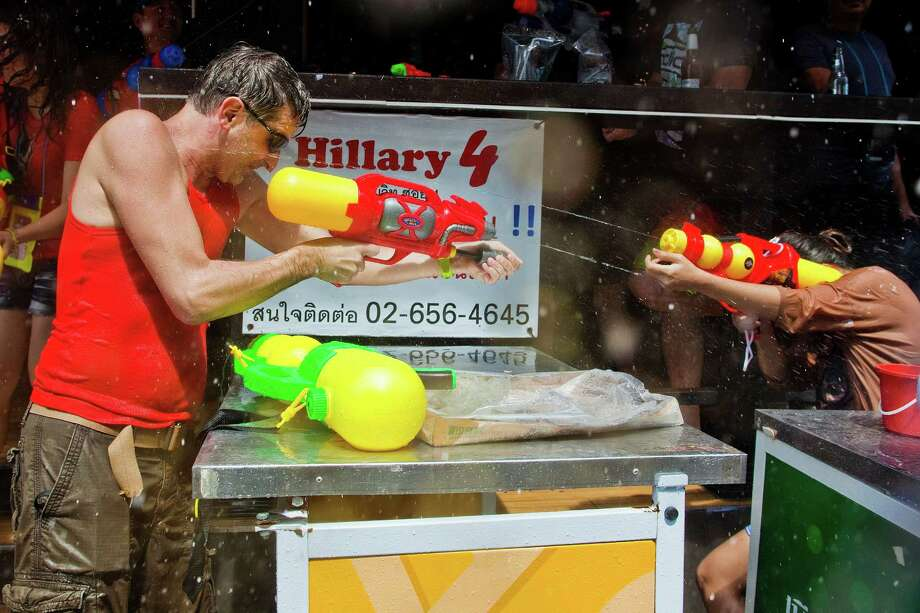BANGKOK, THAILAND - APRIL 14:  A tourists shoots a squirt gun into a bar on Soi Nana during the Songkran water festival on April 14, 2013 in Bangkok, Thailand. The Songkran festival marks the traditional Thai New Year and is celebrated each year from April 13 to 15. The throwing of water originated as a way to pay respect to people and is meant as a symbol of cleansing and purification. (Photo by Jack Kurtz/Getty Images) Photo: Jack Kurtz, WIre / 2013 Getty Images