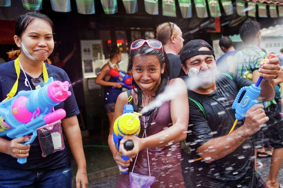 BANGKOK, THAILAND - APRIL 14:  Thais and tourists have a waterfight on Sukhumvit Soi Nana as part of the Songkran water festival on April 14, 2013 in Bangkok, Thailand. The Songkran festival marks the traditional Thai New Year and is celebrated each year from April 13 to 15. The throwing of water originated as a way to pay respect to people and is meant as a symbol of cleansing and purification. (Photo by Jack Kurtz/Getty Images) Photo: Jack Kurtz, WIre / 2013 Getty Images
