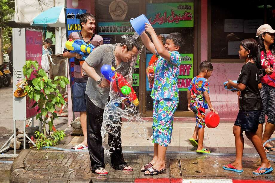 BANGKOK, THAILAND - APRIL 14:  Thai children dump water on a tourist during a waterfight on Sukhumvit Soi Nana as part of the Songkran water festival on April 14, 2013 in Bangkok, Thailand. The Songkran festival marks the traditional Thai New Year and is celebrated each year from April 13 to 15. The throwing of water originated as a way to pay respect to people and is meant as a symbol of cleansing and purification. (Photo by Jack Kurtz/Getty Images) Photo: Jack Kurtz, WIre / 2013 Getty Images