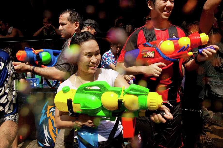 BANGKOK, THAILAND - APRIL 14:  Thais and foreign tourists participate in water fight during the Songkran water festival in Soi Nana on April 14, 2013 in Bangkok, Thailand. The Songkran festival marks the traditional Thai New Year and is celebrated each year from April 13 to 15. The throwing of water originated as a way to pay respect to people and is meant as a symbol of cleansing and purification. (Photo by Jack Kurtz/Getty Images) Photo: Jack Kurtz, WIre / 2013 Getty Images