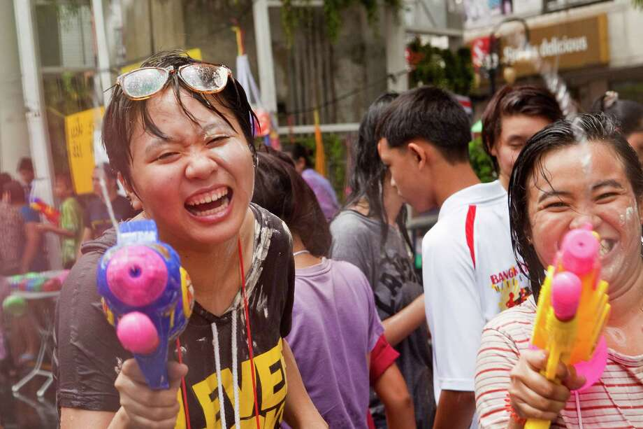 BANGKOK, THAILAND - APRIL 14:  Thais participate in a community water fight as part of the Songkran water festival on April 14, 2013 in Bangkok, Thailand. The Songkran festival marks the traditional Thai New Year and is celebrated each year from April 13 to 15. The throwing of water originated as a way to pay respect to people and is meant as a symbol of cleansing and purification. (Photo by Jack Kurtz/Getty Images) Photo: Jack Kurtz, WIre / 2013 Getty Images