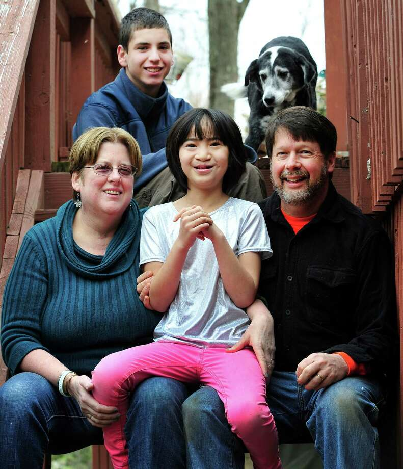 Mike and Margaret Fitzgerald sit outside their New Milford, Conn., home with their daughter, Hannah, 9, and son, Andrew, 15, Monday, April 15, 2013. Nellie, their dog, peers from above. Photo: Michael Duffy / The News-Times