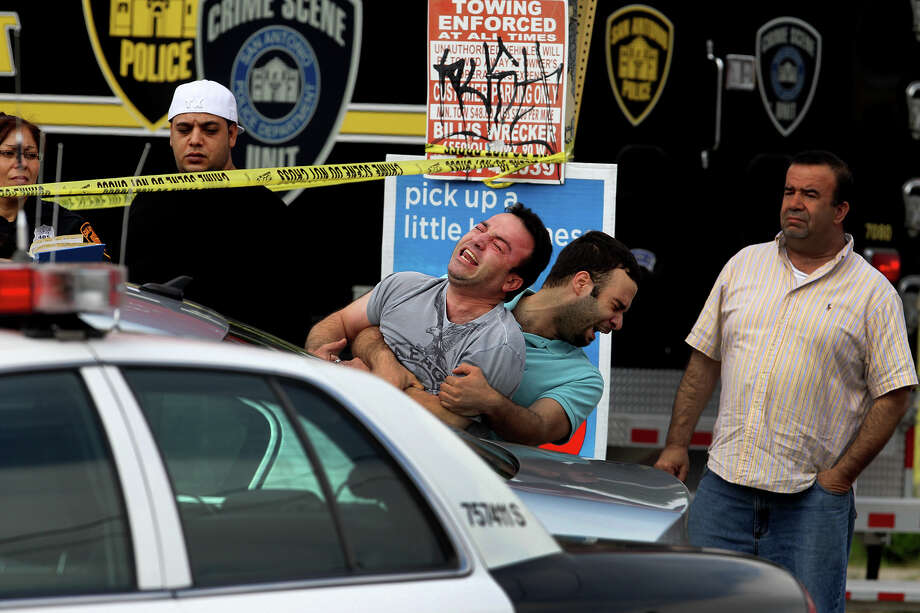 Two men grieve at the scene of a homicide that took place about 7:00 a.m. Monday April 15, 2013 at a convenience store on the 2,500 block of West Southcross. Police at the scene said the man was likely stabbed or shot, but that the Medical Examiner's office is still investigating. Police are looking for the suspect. Photo: JOHN DAVENPORT, SAN ANTONIO EXPRESS-NEWS / ©San Antonio Express-News/Photo may be sold to the public