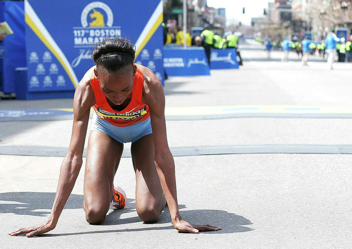 BOSTON, MA - APRIL 15: Rita Jeptoo of Kenya collapses after crossing the finish line to win the women?s division of the 117th Boston Marathon on April 15, 2013 in Boston, Massachusetts.