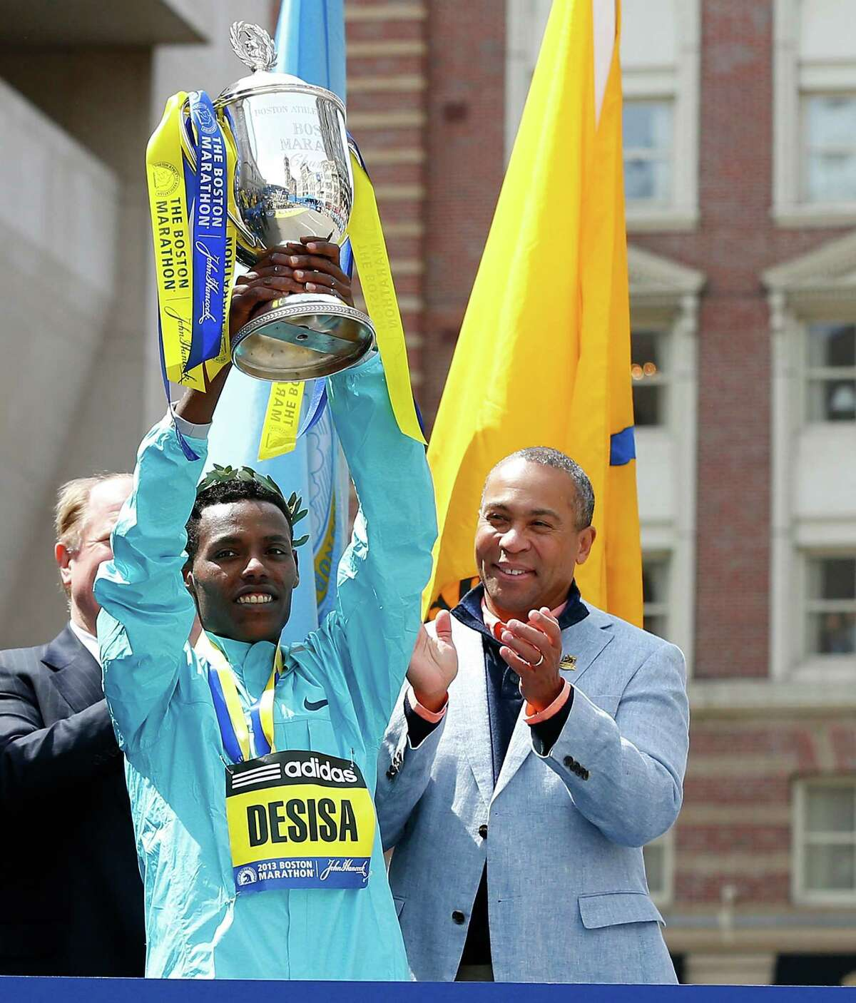 BOSTON, MA - APRIL 15: Lelisa Desisa Benti (L) of Ethiopia holds the trophy after winning the men?s division of the 117th Boston Marathon as Duval Patrick, governor of Massachusetts watches on April 15, 2013 in Boston, Massachusetts.