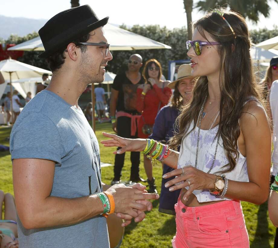 PALM SPRINGS, CA - APRIL 13:  Musician Joe Jonas of the Jonas Brothers (L) and model Alessandra Ambrosio attend the FIJI Water At Lacoste L!VE Coachella Desert Pool Party on April 13, 2013 in Palm Springs, California.  (Photo by Imeh Akpanudosen/Getty Images for FIJI)