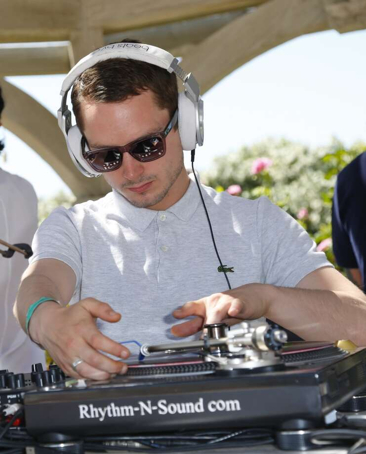 PALM SPRINGS, CA - APRIL 14:  Actor Elijah Wood spins at the FIJI Water At Lacoste L!VE Coachella Desert Pool Party on April 14, 2013 in Palm Springs, California.  (Photo by Imeh Akpanudosen/Getty Images for FIJI)