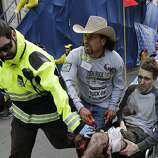 Medical responders run an injured man past the finish line the 2013 Boston Marathon following an explosion in Boston, Monday, April 15, 2013. Two explosions shattered the euphoria of the Boston Marathon finish line on Monday, sending authorities out on the course to carry off the injured while the stragglers were rerouted away from the smoking site of the blasts. (AP Photo/Charles Krupa)