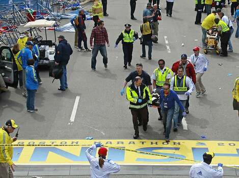 Medical workers wheel the injured across the finish line during the 2013 Boston Marathon following an explosion in Boston, Monday, April 15, 2013. Two explosions shattered the euphoria of the Boston Marathon finish line on Monday, sending authorities out on the course to carry off the injured while the stragglers were rerouted away from the smoking site of the blasts. (AP Photo/Charles Krupa) Photo: Charles Krupa, Associated Press