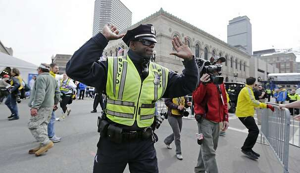 A Boston police officer clears Boylston Street following an explosion at the finish line of the 2013 Boston Marathon in Boston, Monday, April 15, 2013. Two explosions shattered the euphoria at the finish line on Monday, sending authorities out on the course to carry off the injured while the stragglers were rerouted away from the smoking site of the blasts. (AP Photo/Charles Krupa) Photo: Charles Krupa, Associated Press