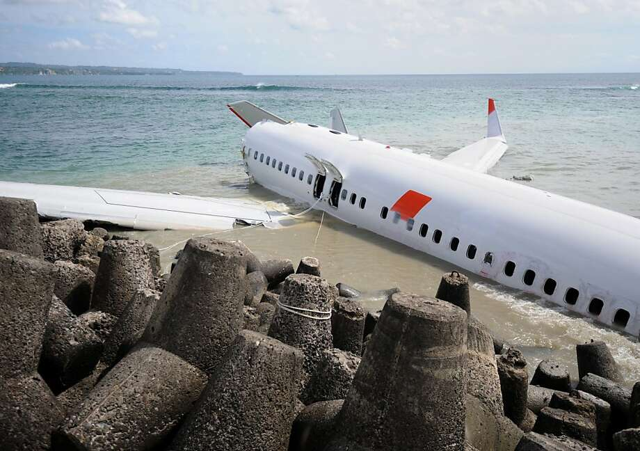 "Beached Boeing:Two days after crashing while trying to land at Bali's international airport, a Lion Air Boeing 737 sits in the shallow surf near Denpasar soaking up rays. Dozens were hurt but miraculously nobody killed when the plane belly-flopped in the water. The pilot said he felt the aircraft ""dragged"" down by the wind while he struggled to regain control. Photo: Sonny Tumbelaka, AFP/Getty Images"