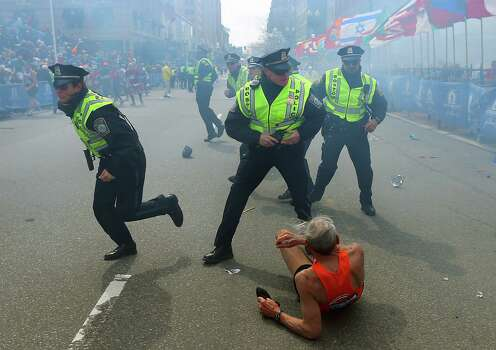 BOSTON - APRIL 15: Police officers with their guns drawn hear the second explosion down the street. The first explosion knocked down a runner at the finish line of the 117th Boston Marathon. Photo: Boston Globe, Getty Images / 2013 - The Boston Globe