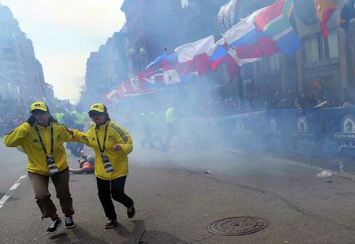 BOSTON - APRIL 15: Two officials run away from the first explosion, right, on Boylston Street at the 177th Boston Marathon, April 15, 2013. Photo: Boston Globe, Getty Images / 2013 - The Boston Globe