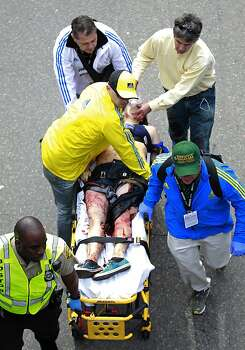 Medical workers aid an injured man at the finish line of the 2013 Boston Marathon following an explosion in Boston, Monday, April 15, 2013. Two bombs exploded near the finish of the Boston Marathon on Monday, killing two people, injuring 22 others and sending authorities rushing to aid wounded spectators, race organizers and police said. (AP Photo/Charles Krupa) Photo: Charles Krupa, Associated Press