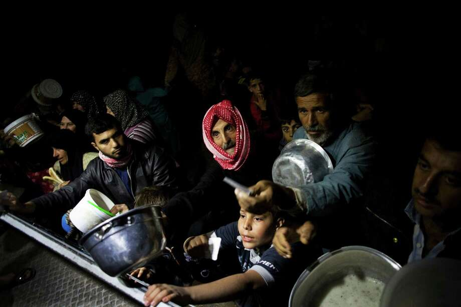 Displaced Syrian men wait for food in a refugee camp last year. The Obama administration is proposing an overhaul to the American food aid program. Photo: Manu Brabo, Associated Press / AP
