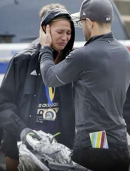 An unidentified Boston Marathon runner is comforted as she cries in the aftermath of two blasts which exploded near the finish line of the Boston Marathon in Boston, Monday, April 15, 2013. Photo: Elise Amendola, Associated Press/Elise Amendola