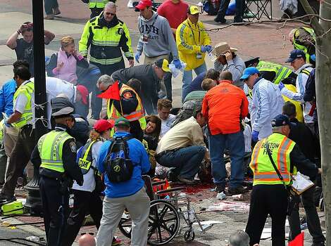 Medical workers aid injured people at the 2013 Boston Marathon following an explosion in Boston, Monday, April 15, 2013. Two explosions shattered the euphoria of the Boston Marathon finish line on Monday, sending authorities out on the course to carry off the injured while the stragglers were rerouted away from the smoking site of the blasts. (AP Photo/The Boston Globe, David L Ryan) Photo: David L. Ryan, Associated Press
