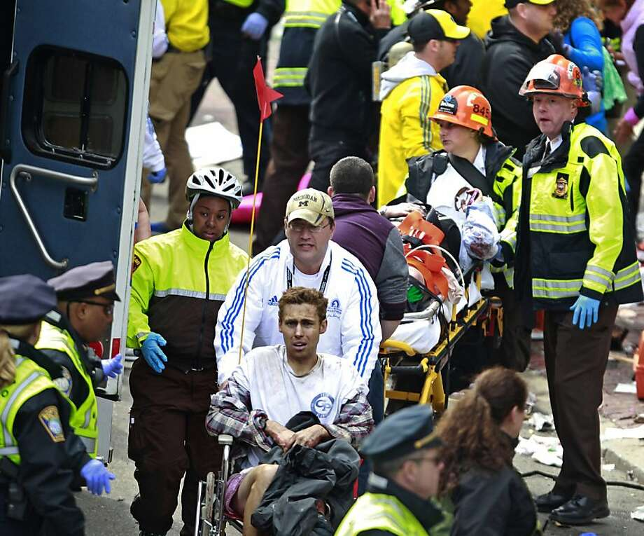 Medical workers aid injured people at the finish line of the 2013 Boston Marathon following an explosion Monday, April 15, 2013 in Boston. Two bombs exploded near the finish line of the marathon on Monday, killing at least two people, injuring at least 22 others and sending authorities rushing to aid wounded spectators. Photo: Charles Krupa, Associated Press